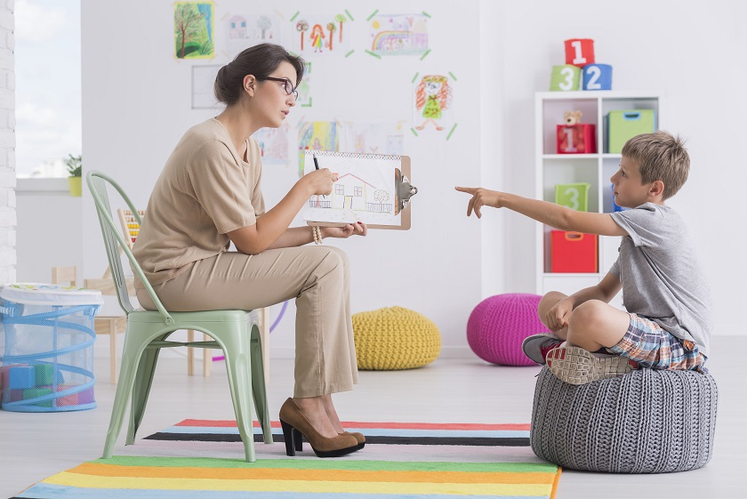 Therapist to conduct an aba therapy one to one session with a child kid Asperger.